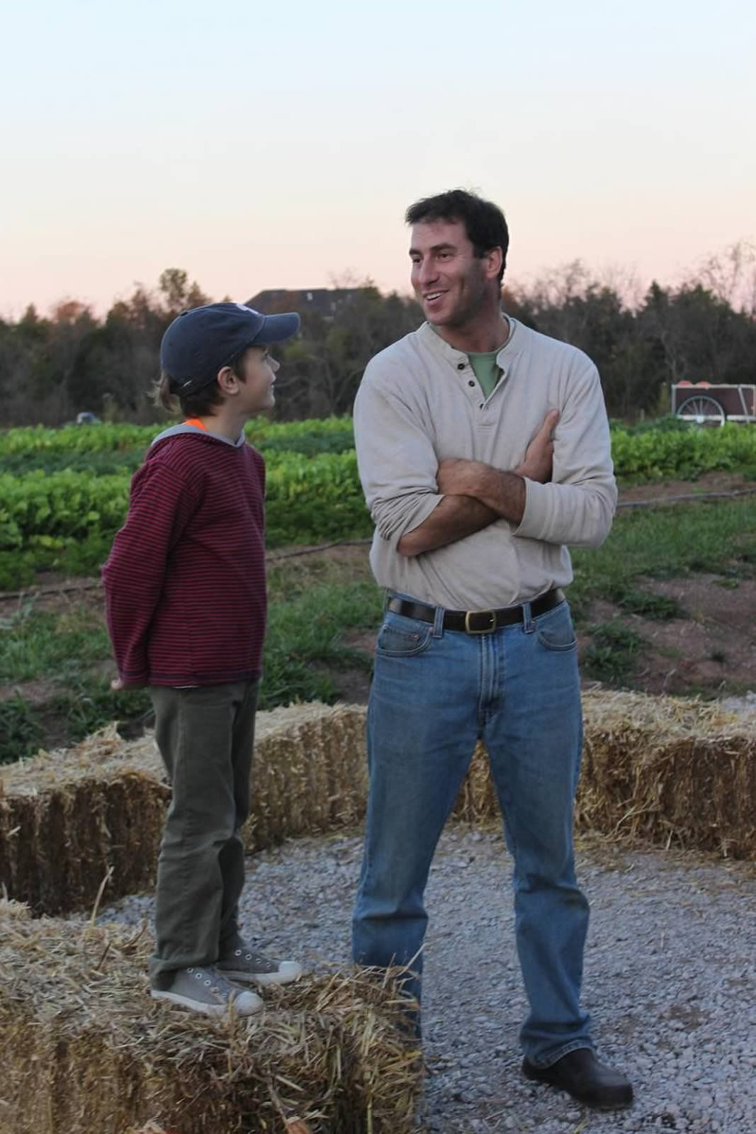 Farmer Mike teaching a young boy the ropes of farming...Farm potluck Fall 2012