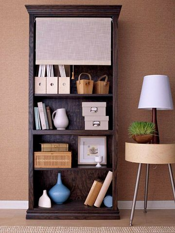 Update a bookshelf!  Pull the shade on unsightly essentials while showing off your organized storage bins. Start by giving the bookcase a rich color with a deep ebony gel stain finish. To create the handy shade, purchase a linen roller shade to fit in the width of the bookcase then install the hardware on the inside edges of the frame. Finish off the shade pull with a decorative finial or tassel.