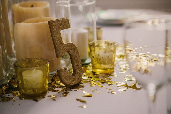 Table numbers were decorated in gold glitter.  Ceremony Venue: St. Catherine of Siena Catholic Church  Reception Venue:Mercury Hall  Event Planner:Something To Celebrate  Rentals:Marquee Event Group
