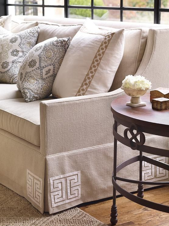 Living Room With A Linen Skirted Sofa Greek Key Trim Is Flanked By Round Iron