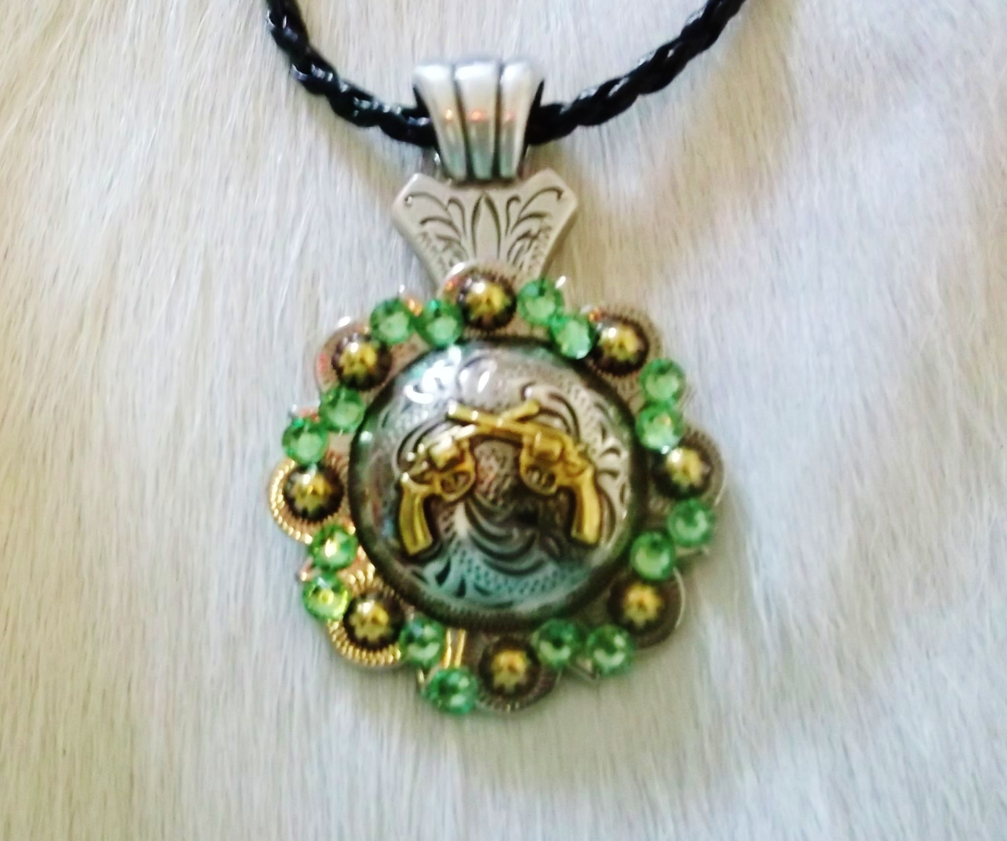 Pistol necklace accented with glass peridot green crystals. 17in cord with 2in chain extension.  www.pamperedcowgirl.com