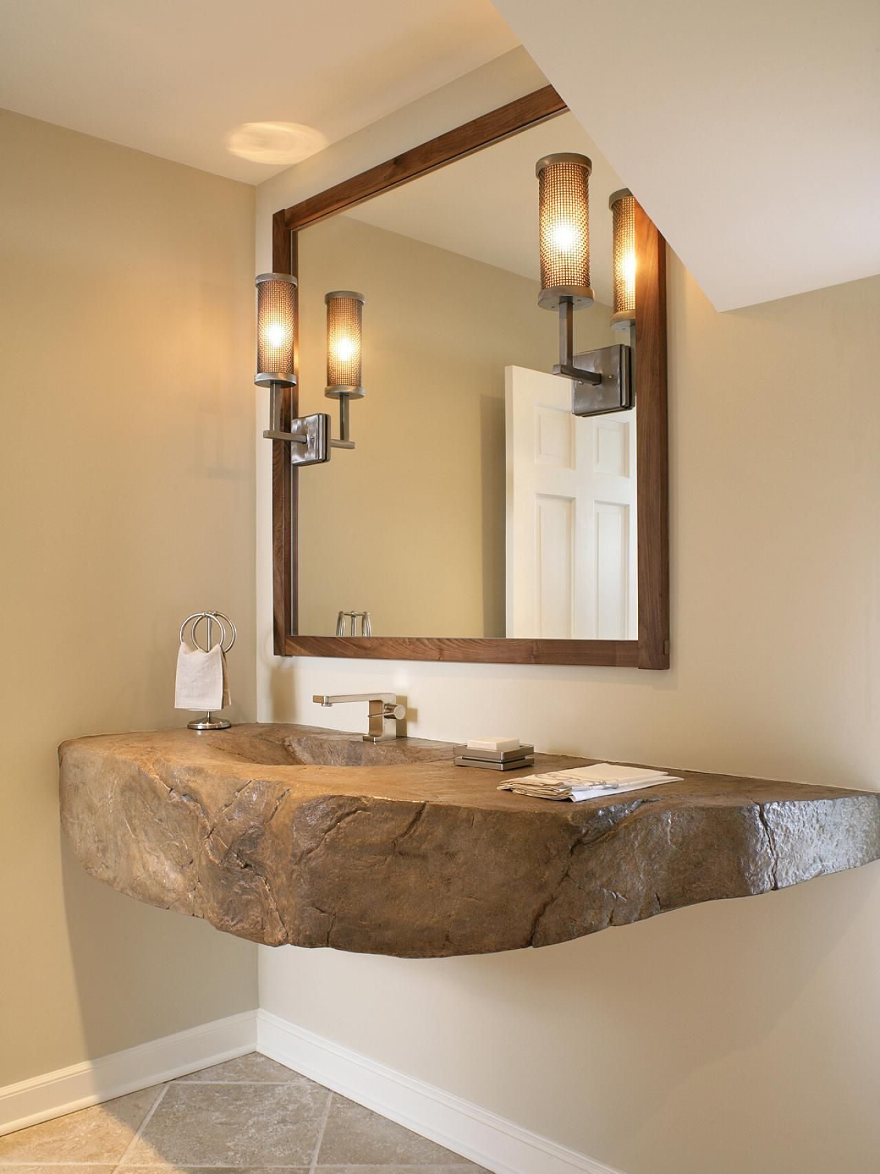 A Striking, Unique Floating Vanity Made From Rock Accompanies A Large  Mirror And Wall Sconces