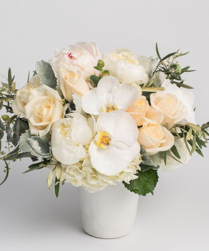 Peony Opulence - This pristine arrangement of all whites and creams - including roses, peonies, hydrangea and orchids - is designed in a white ceramic container with simple textural accents. #mothersday #flowers