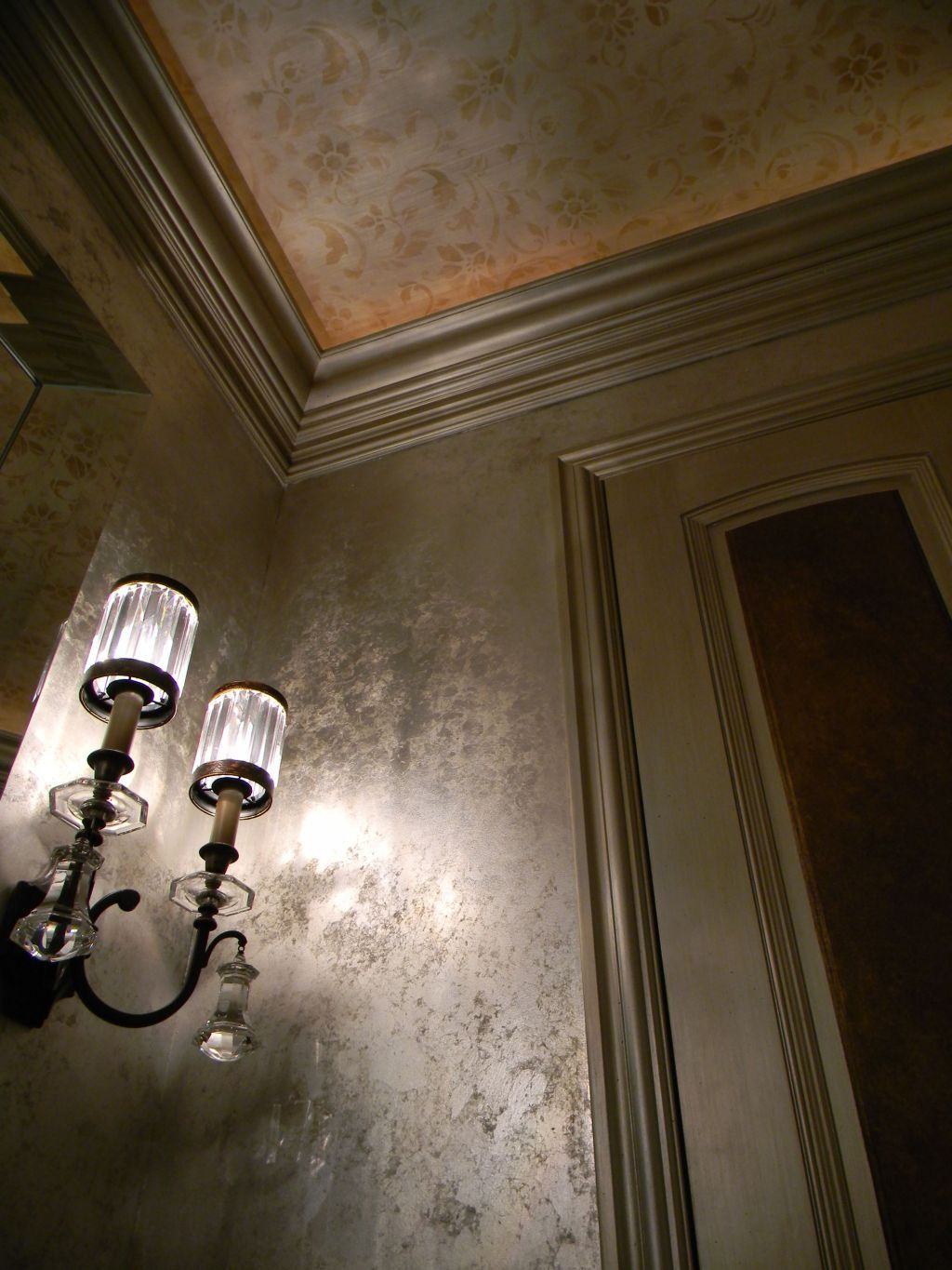 this little jewel box powder room has: silver leaf walls, layered