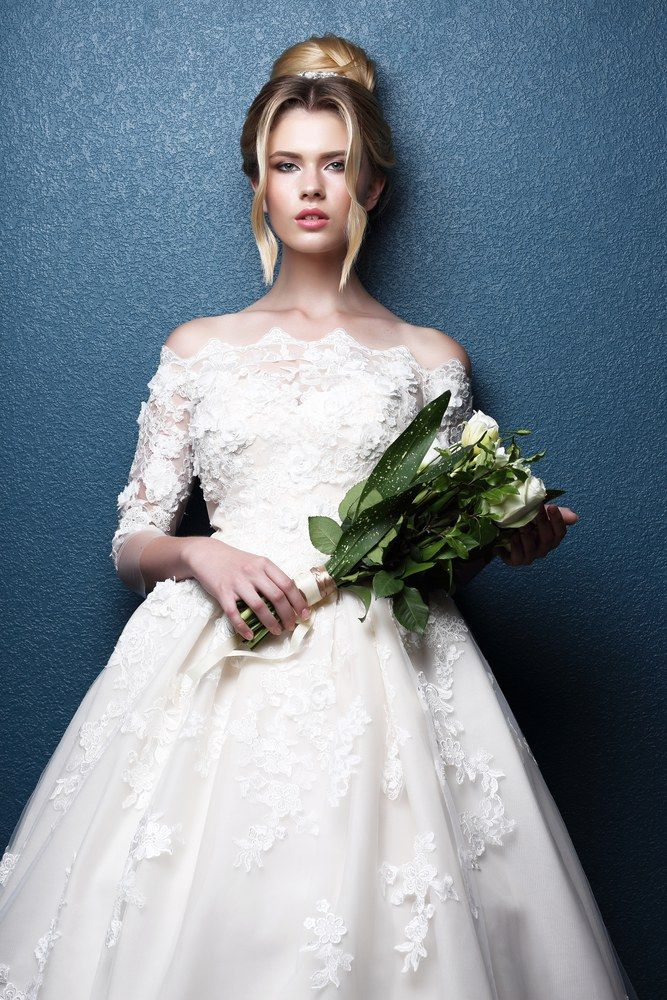 Young beautiful bride. Wedding hairstyle, blond hair, wedding dress, makeup and bride's bouquet. Indoor shot