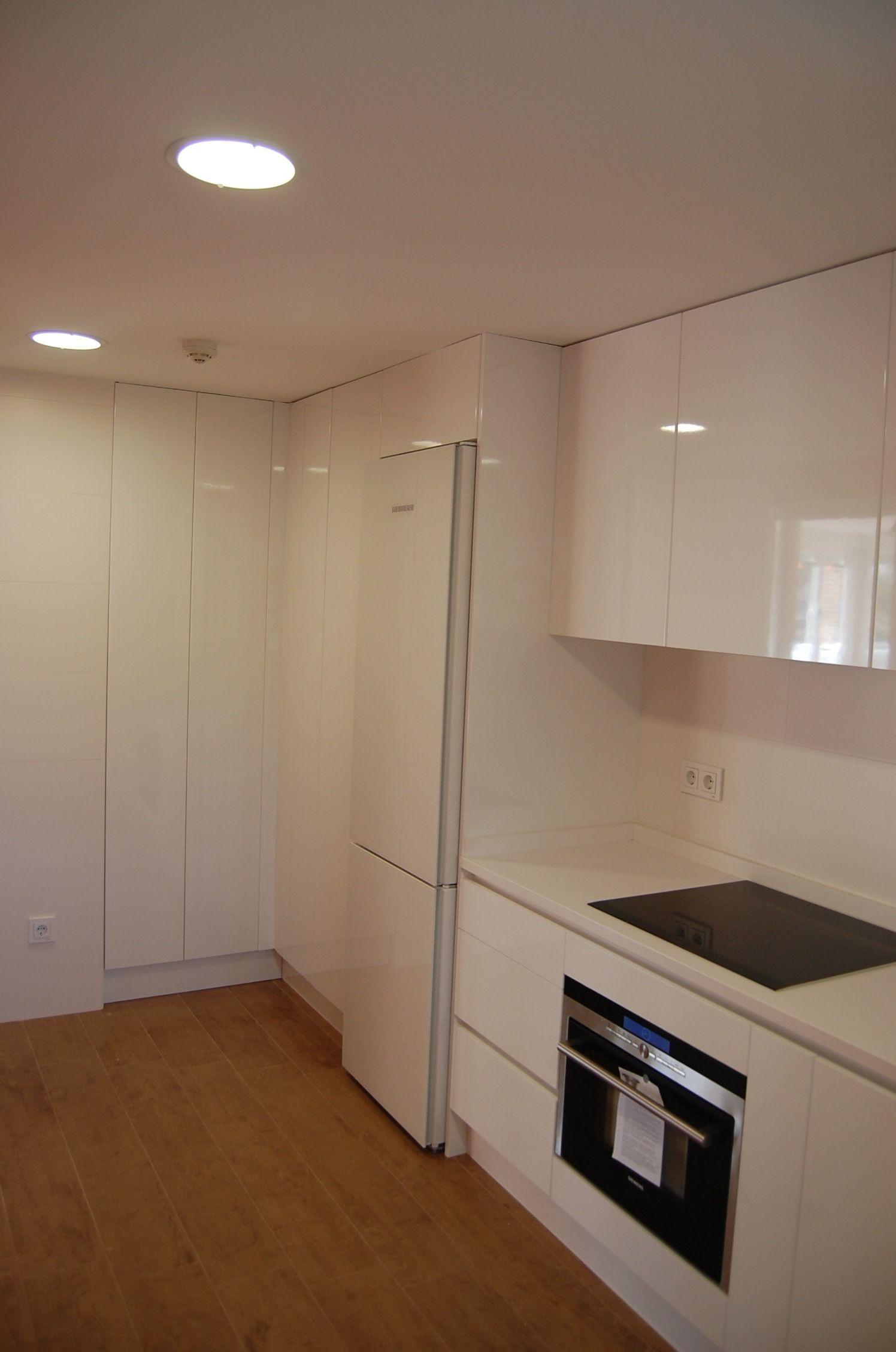 cocina moderna minimalista en blanco con suelo de madera en