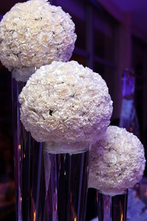 Pomanders Of White Carnations Float In Tall Vases Filled With Water