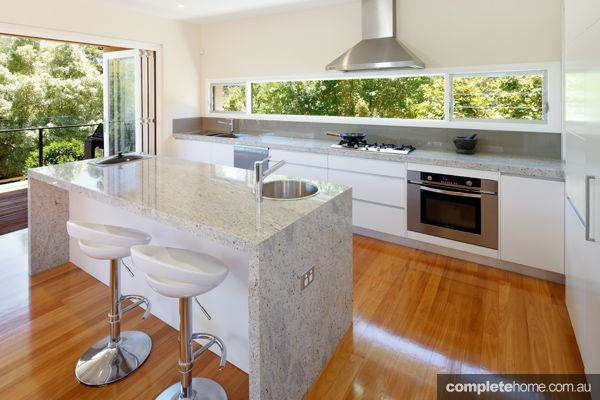 gloss white kitchen with granite surfaces, stainless steel