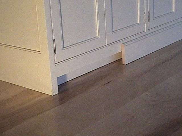 Add a strip of wood beneath cabinet to adhere base molding