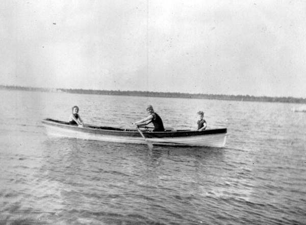 Mrs. Ahern rowing a boat with her children aboard on Crooked Lake - Babson Park, Florida