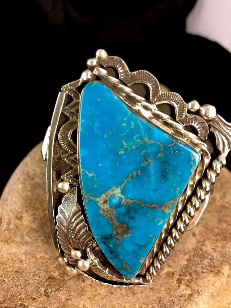 "Beautiful bracelet with a large triangular turquoise in Sterling silver. Classic design with feathers in a heavy bracelet. Weight 116.6 gms Width 1.91- 2.5"" Gap 1"" Inner circumference 5"" 