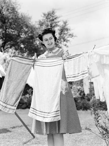 size: 24x18in Photographic Print: Woman Wearing a White Collar Poka Dot Cotton Dress While Pinning a Towel on a Clothes Line by H. Armstrong Roberts : Artists