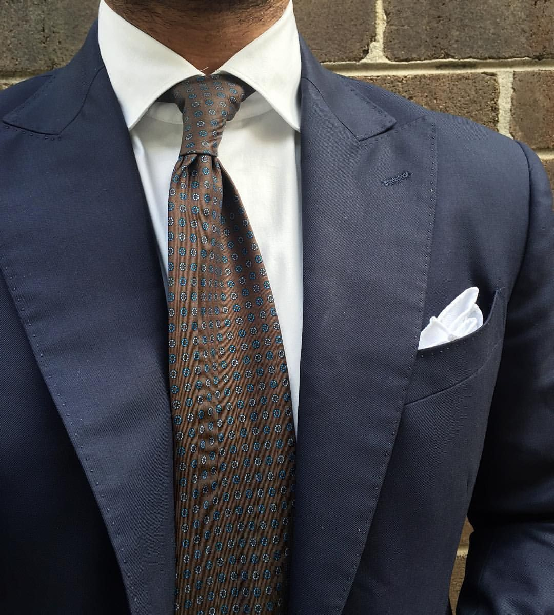 Navy jacket with peak lapels, white shirt, brown tie