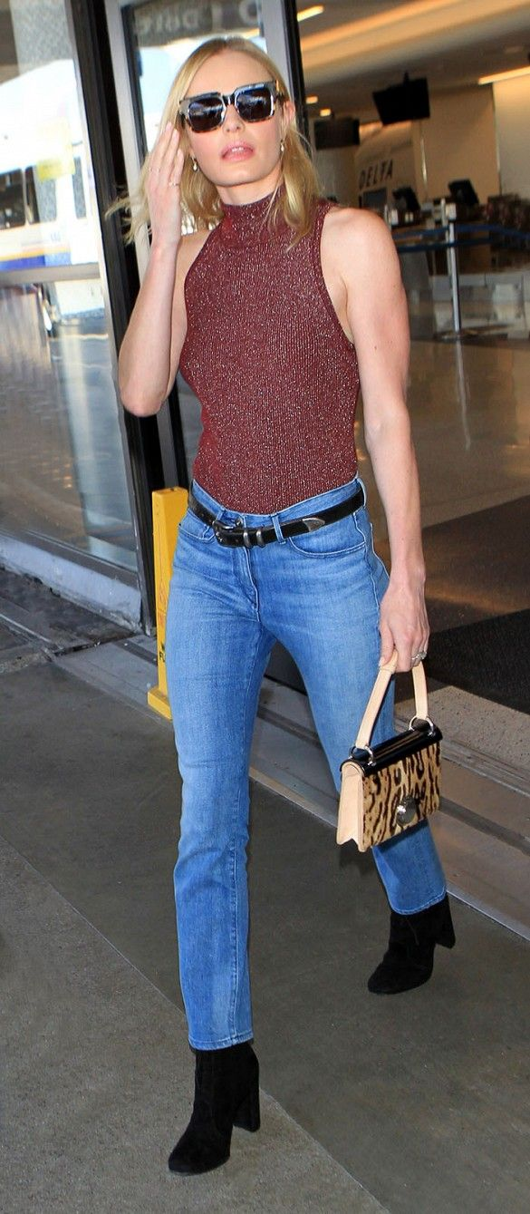 fb12f5a9c04 Kate Bosworth wears a sparkling turtleneck tank top tucked into belted blue  jeans, square sunglasses, a leopard top handle bag, and black suede booties