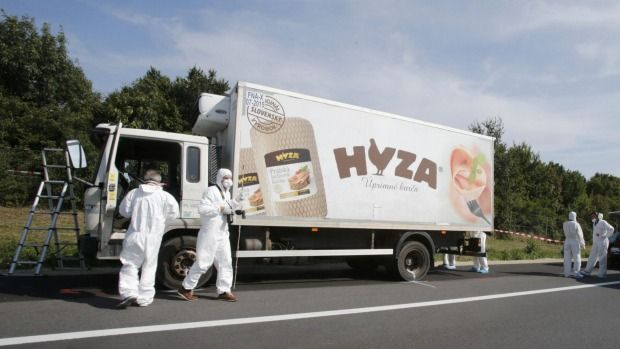 Forensic police officers inspect the truck parked on an Austrian highway.