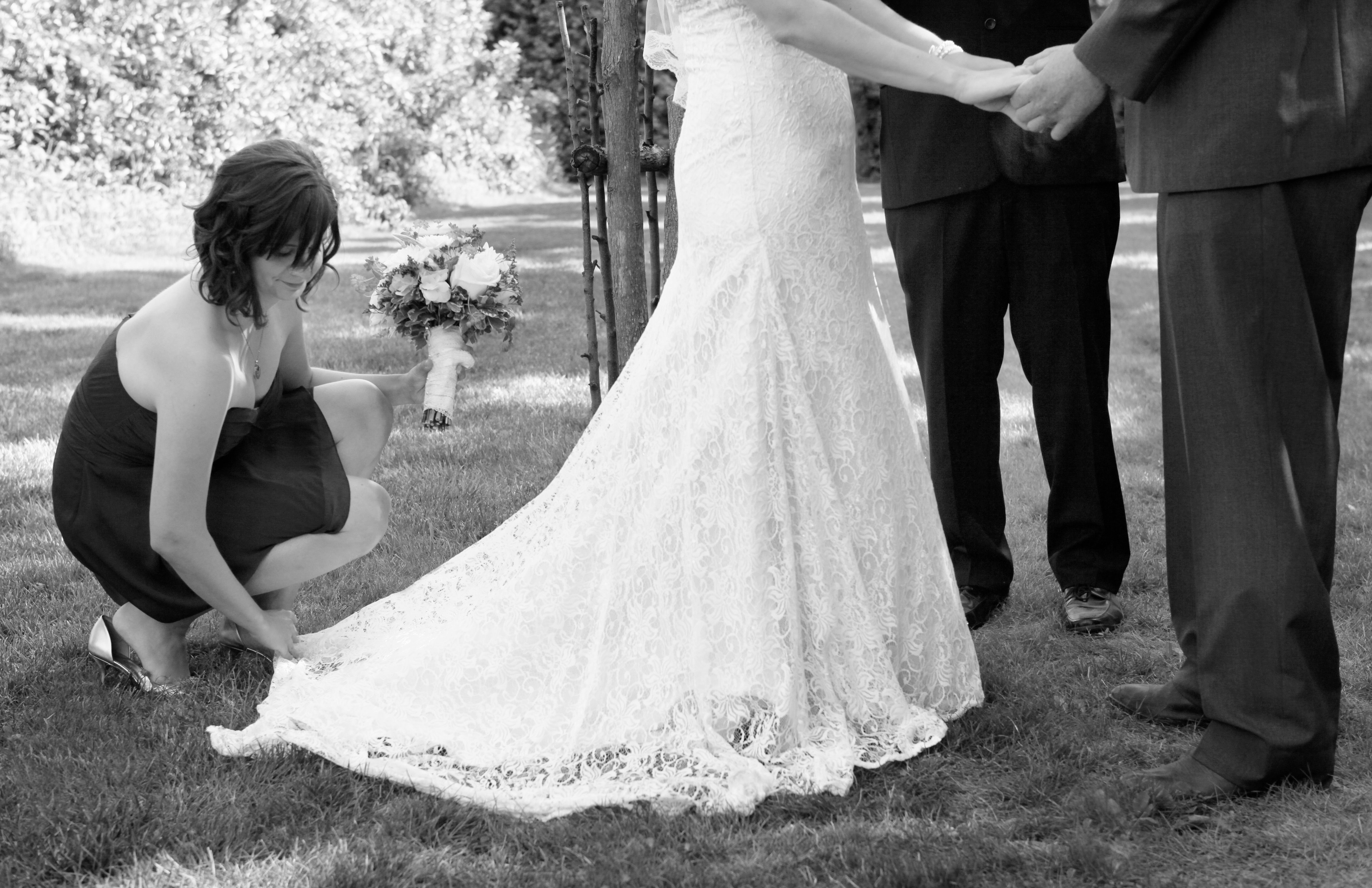 Bridesmaid, Maid of Honor adjusting the bride\'s lace wedding dress ...