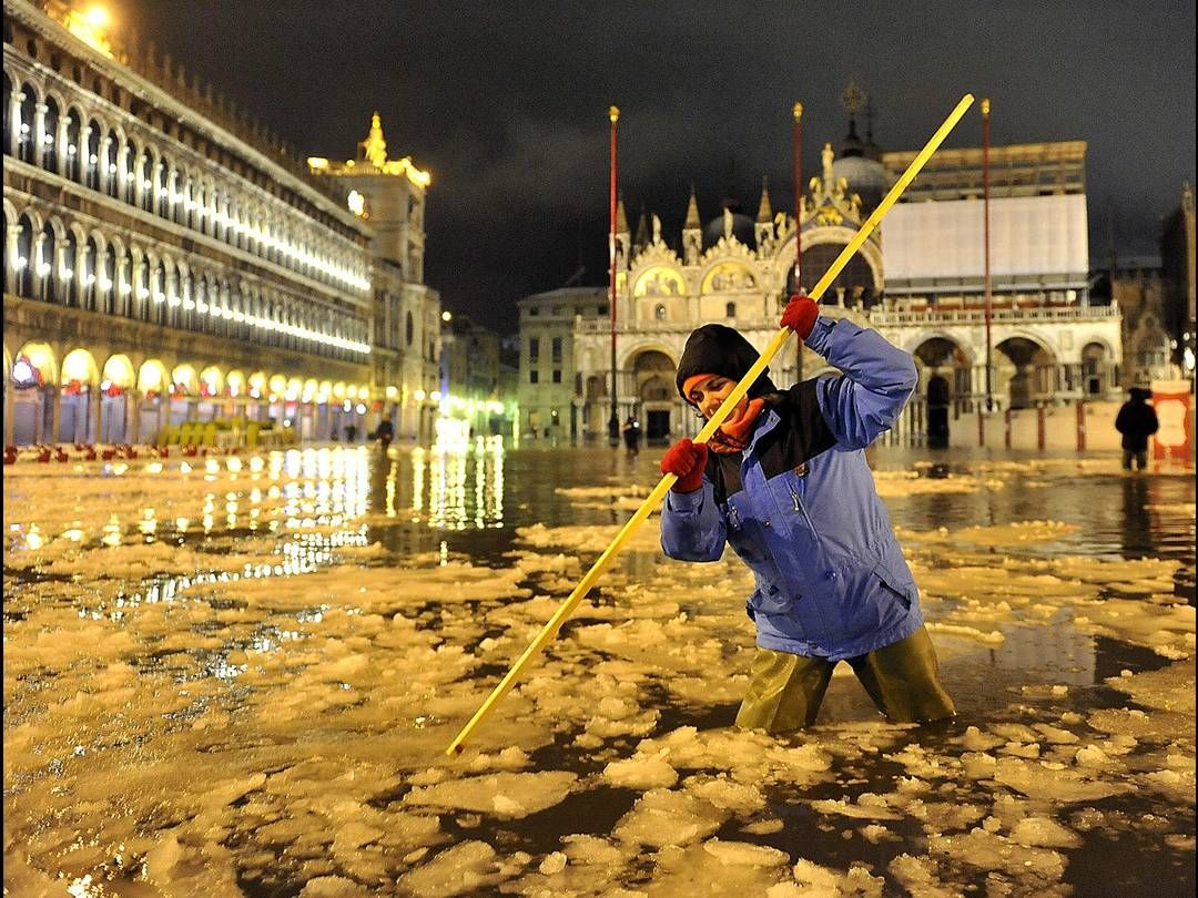 A woman wades through high water and floating ice on a flooded St. Mark's Square in Venice, Italy.