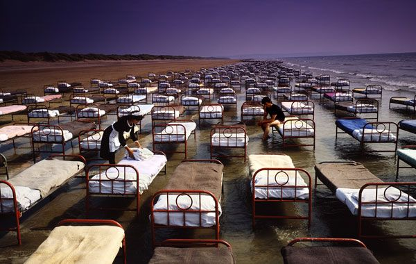 """Storm Thorgerson (1944-2013)  Pink Floyd - A Momentary Lapse Of Reason 1987 """"These beds are real wrought iron Victorian hospital beds each weighed an effing ton. They are laid out in the vague shape of a riverbed, ho ho, and what you see is what you get - approx 700 hundred beds on a seashore. It took 30 people, 2 tractors and 3 flatbeds all day to arrange them, then it rained and we had to come back two weeks later and do it all again… """""""