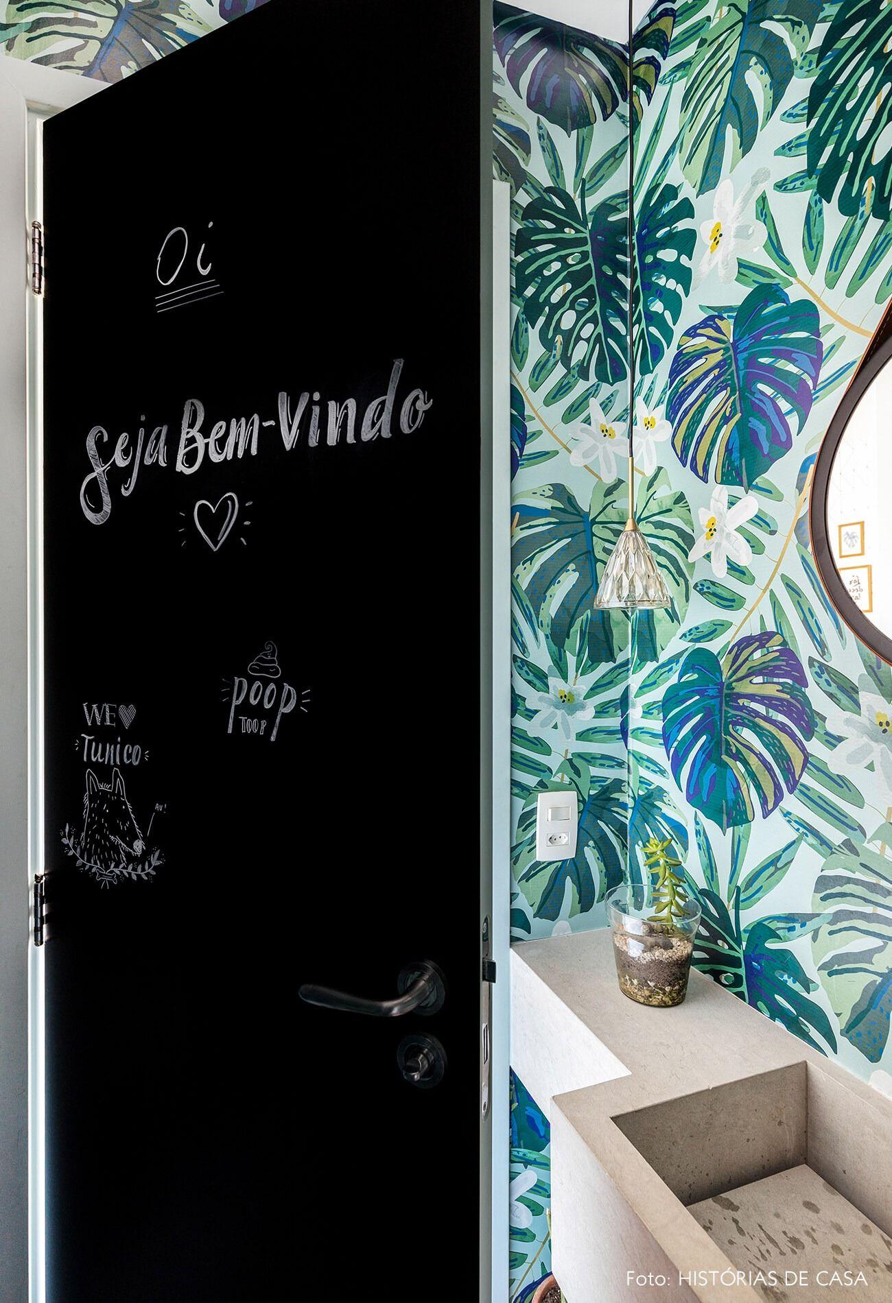 Lavabo com papel de parede de Costela-de-Adão tem adesivo de lousa na porta   Wall stickers give this light apartment full of plants even more color and textures. Get inspired too!