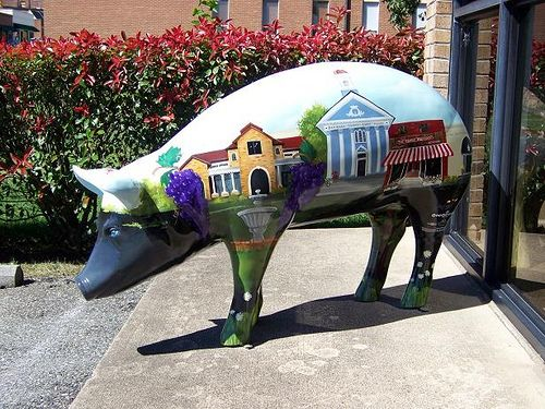 # 18 of the 2009 Pigs in the City V, of Lexington, NC. (Pork BBQ Capital of the World). Was sponsored by Lexington Tourism Authority, and the artist was Margaret Sink. It was located on E. Center St. in front of The Lexington Tourism Authority building.  It featured several well known buildings, and scenes Lexington and the nearby area.