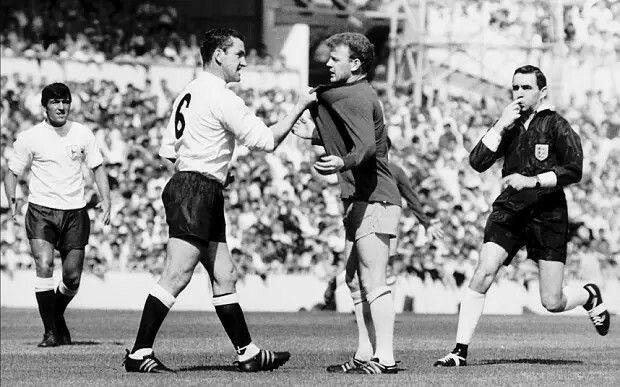 Dave Mackay of Spurs and and Billy Bremner of Leeds - Both Scotsmen,  Dave was just back from a layoff with a broken leg and had been caught badly by Bremner. A young and plump Terry Venables watches on.