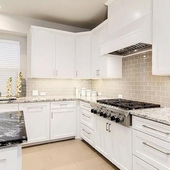 White shaker kitchen cabinets with gray glass tiles also