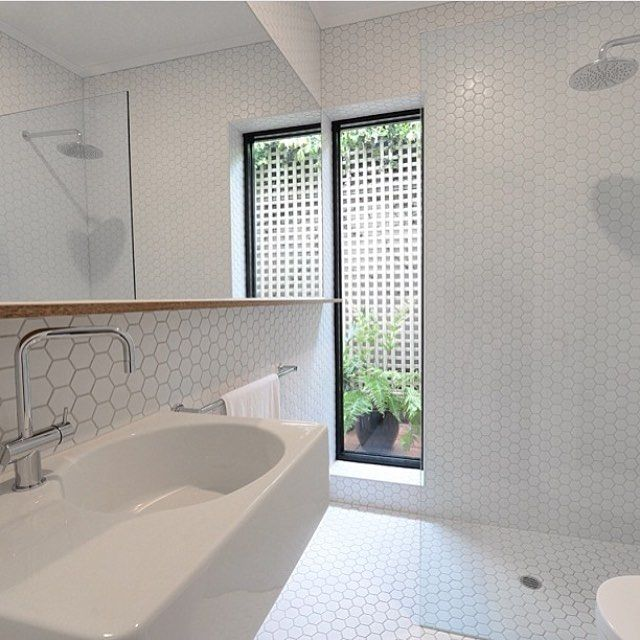 White hex tiled walls and floors, white bench top basin and vanity