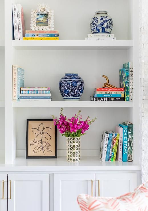 White shaker cabinets adorned with brass pulls are fitted beneath white styled bookshelves. #whiteshakercabinets