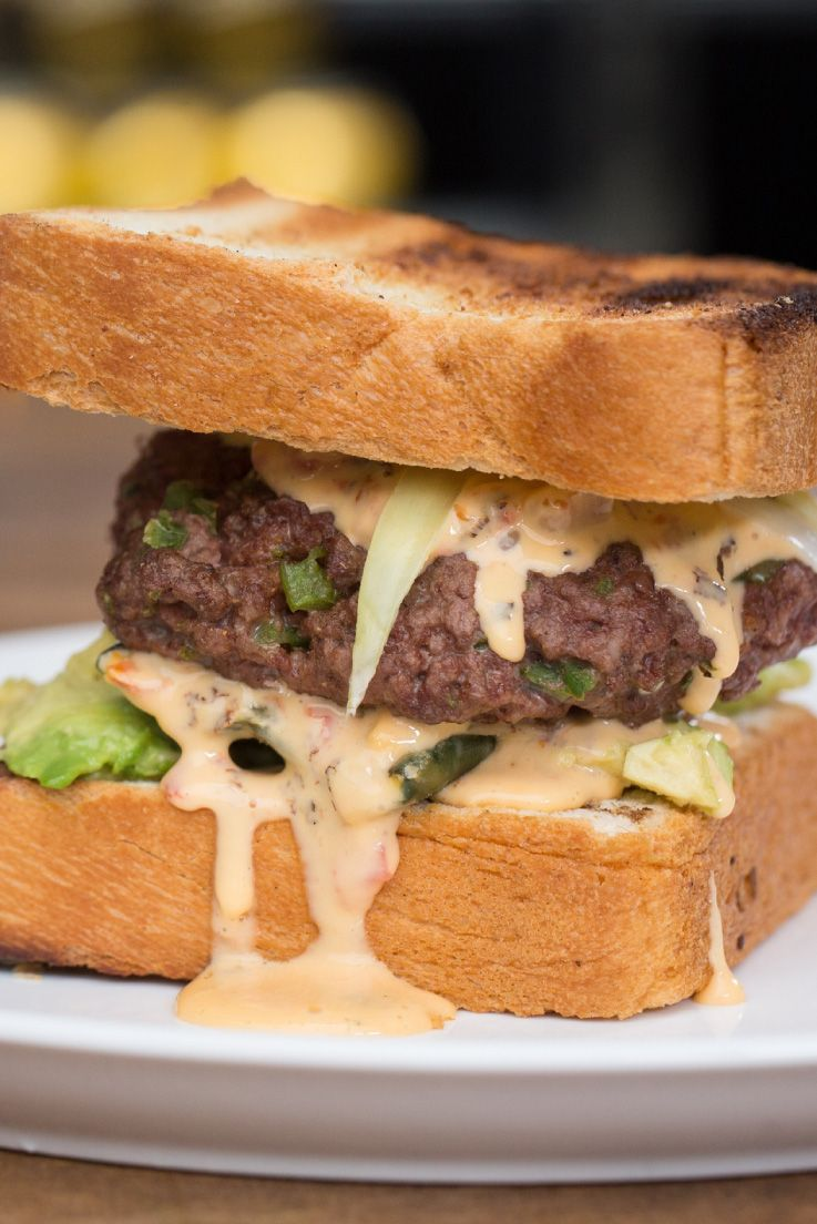 """This burger, by """"Backyard Battles"""" winner Dannelle Rivera, is dusted with cajun seasoning before getting smoked and grilled, slathered with queso, and sandwiched between two hefty slices of Texas toast. Why didn't we think of this before?"""
