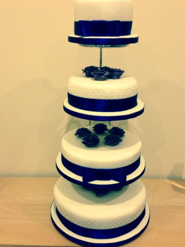 Ivory and purple wedding cake with handmade roses