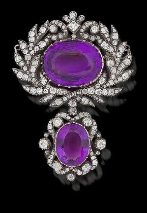 An amethyst and diamond brooch, circa 1820  The large oval mixed-cut amethyst, within a stylised laurel wreath border of old brilliant and rose-cut diamonds, suspending a detachable drop of similarly set amethyst and diamonds, mounted in silver and gold by Dittekarina