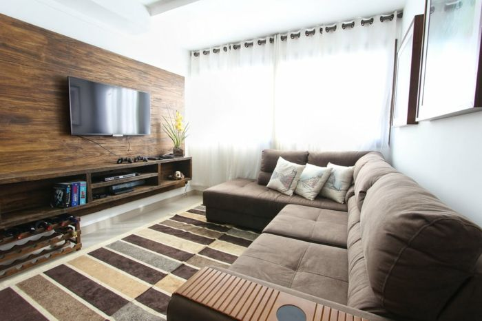 grauner Wohnzimmer Fernsehwand, weiße Gardinen, braunes Sofa, Vase