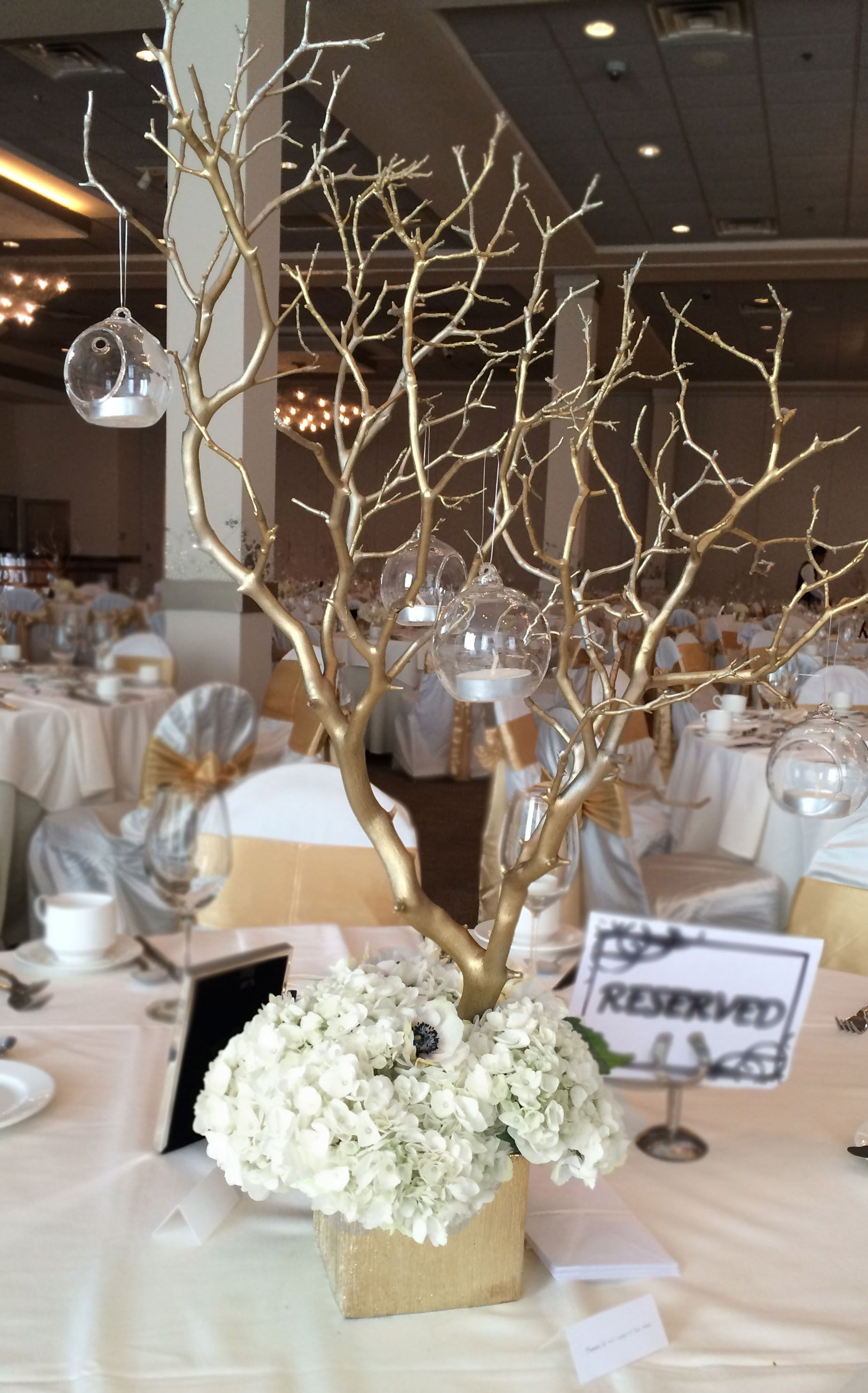 Reception centerpieces arrangement includes gold sprayed