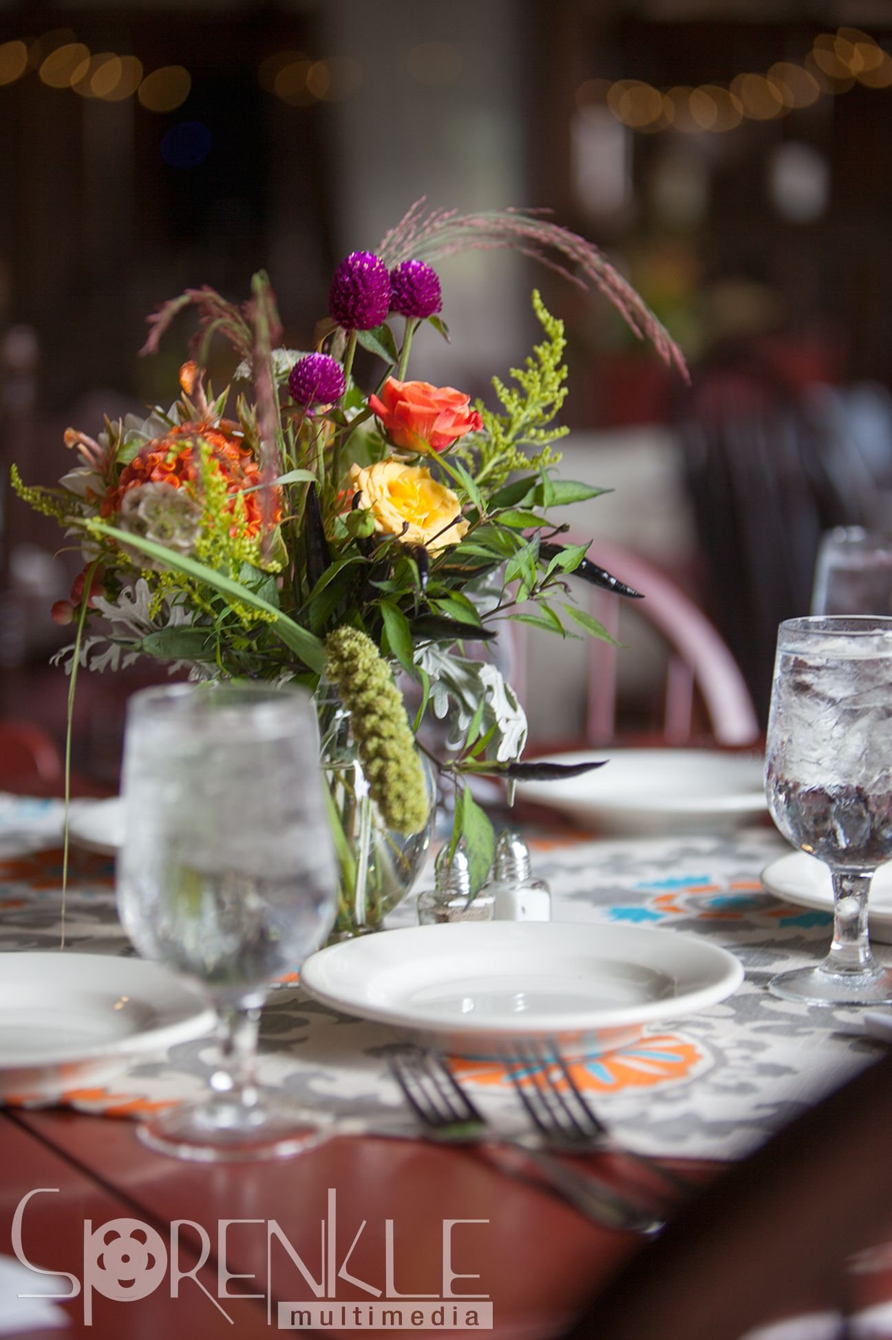 Multi-colored flower arrangement and table setting at wedding.