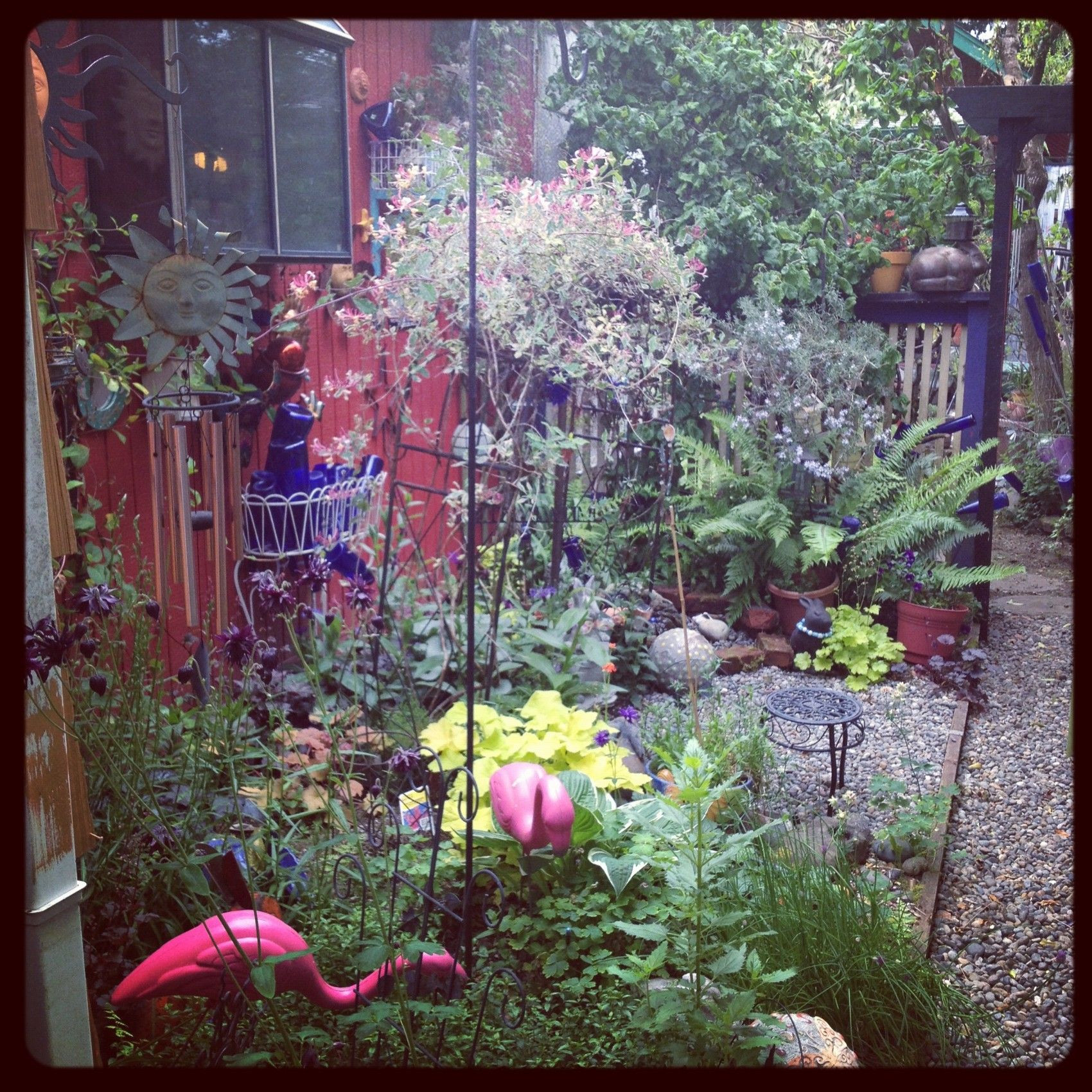 My private garden has a bench and rabbits and flamingoes and bottles and bird houses and a sweet fountain the chickadees love.