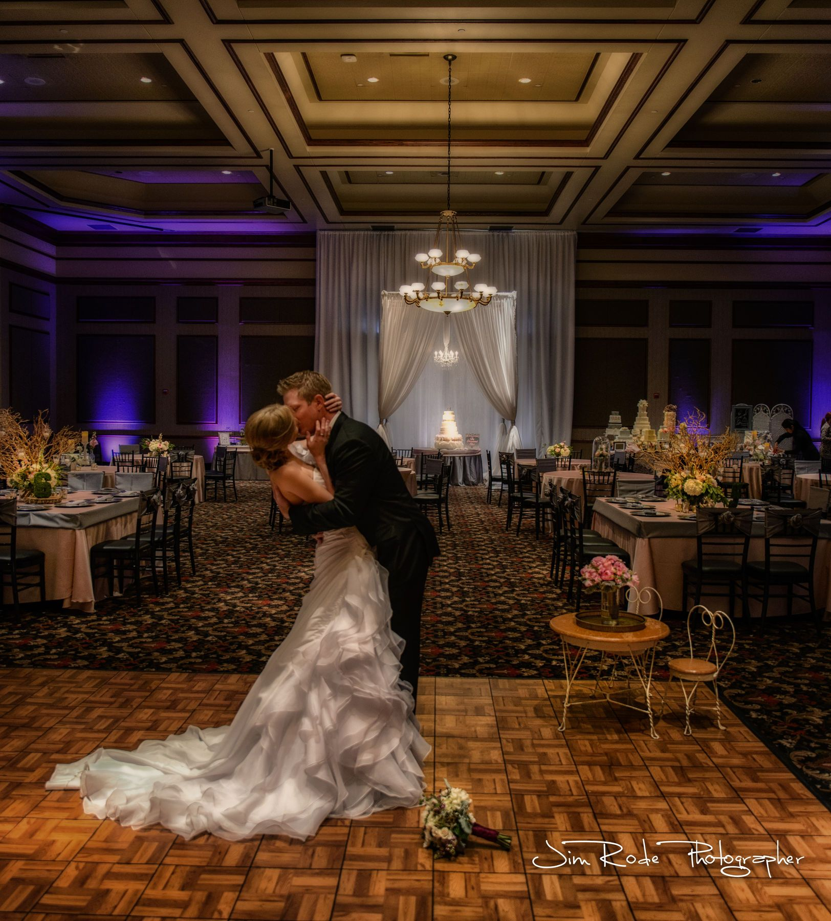 Shooting HDR allows the capture of the wedding details I love! Gown, bouquet on the floor, the draped cake, and that cute table for the kids to sit to watch the dancing on that parquet dance floor. Too much flash would turn her gown into a pasted-over snowy smear, light up the dance floor in one direction or another -spoiling the center of attention, and make even the cake disappear into a dark background. With HDR, everything is balanced. photo by Jim Rode Photographer