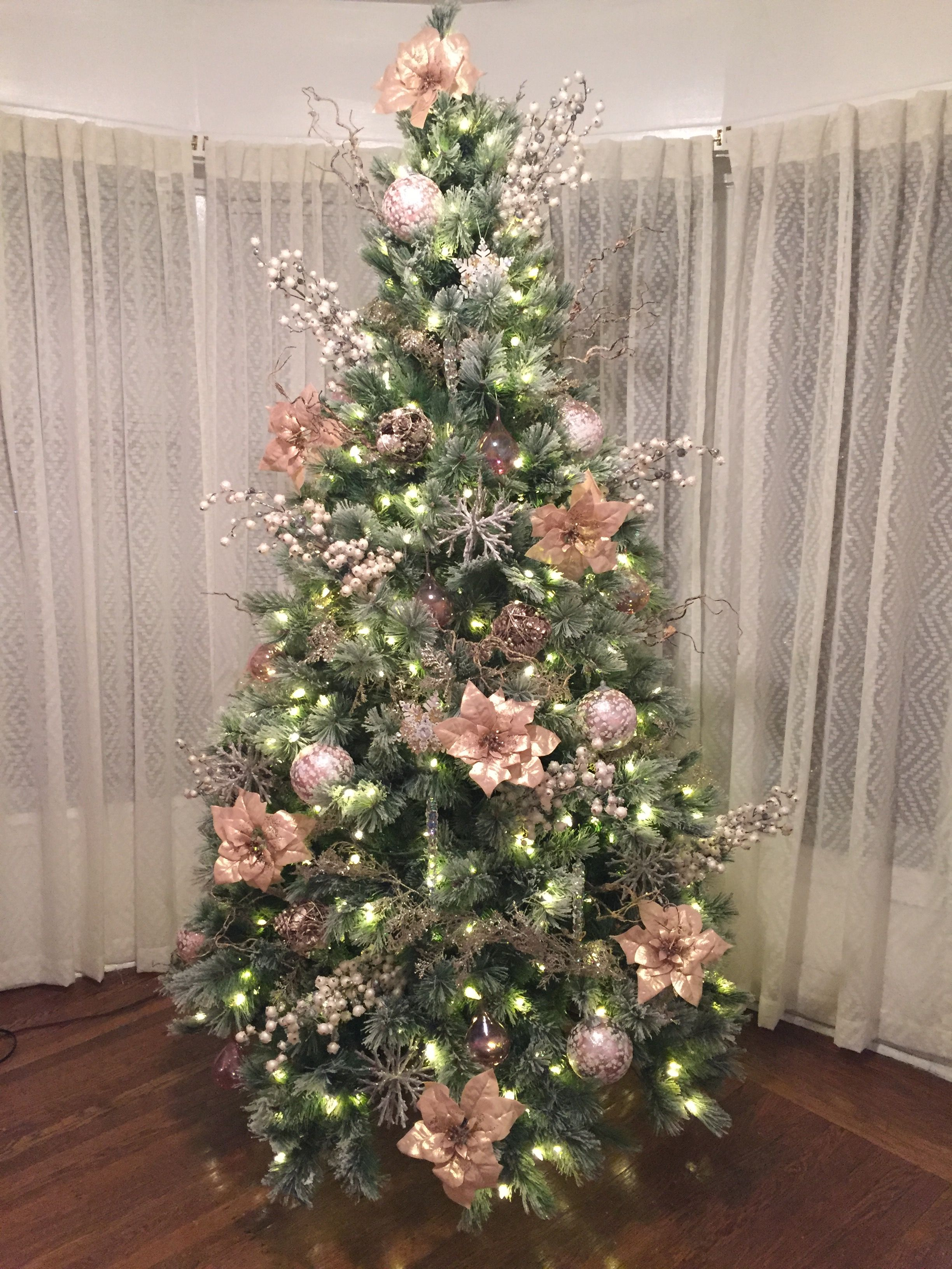 Pink Poinsettias Decorate This Christmas Tree White Lights And Sprays Christmas Tree Christmas Tree Themes Christmas Tree Toppers