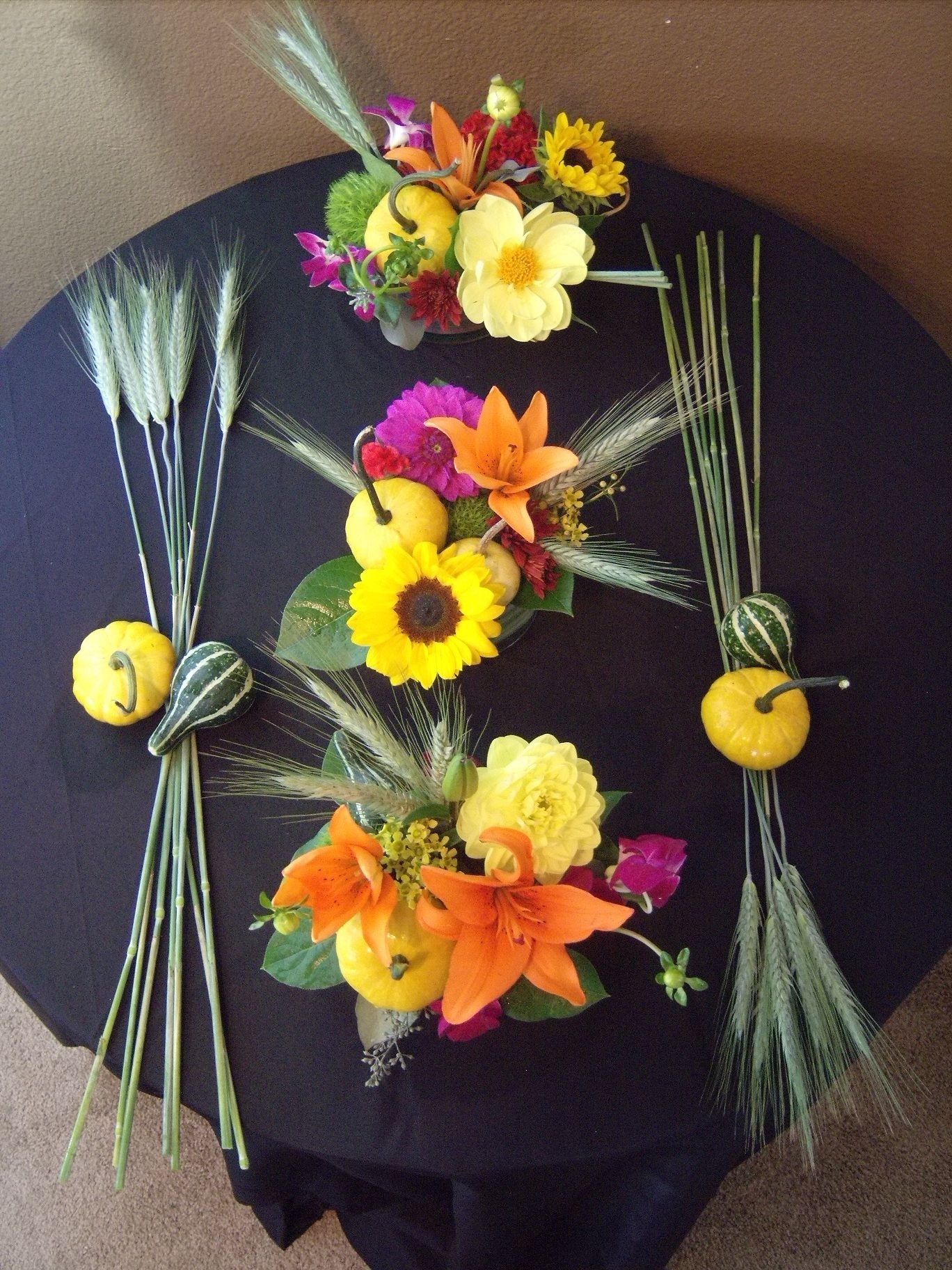 Fall floral arrangement using a mix of gourds wheat dahlia