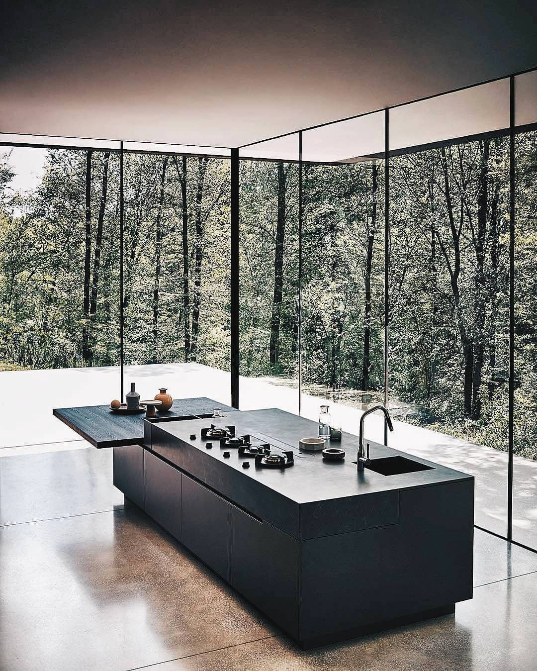 minimal black kitchen island bench surrounded by tall windows with