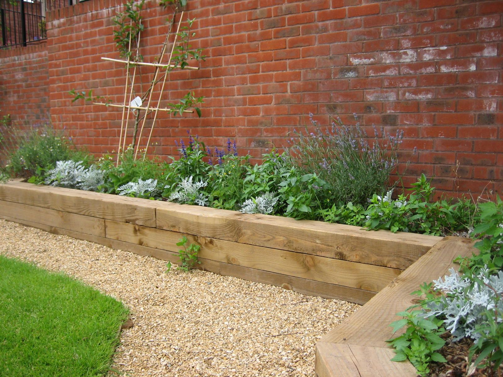 Raised beds railways sleepers gravel path brick wall for Garden designs sleepers