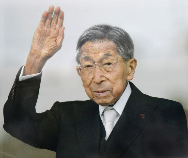 In this Jan. 2, 2015 photo, Japan's Prince Mikasa waves to well-wishers from a balcony during a New Year's public appearance at the Imperial Palace in Tokyo....