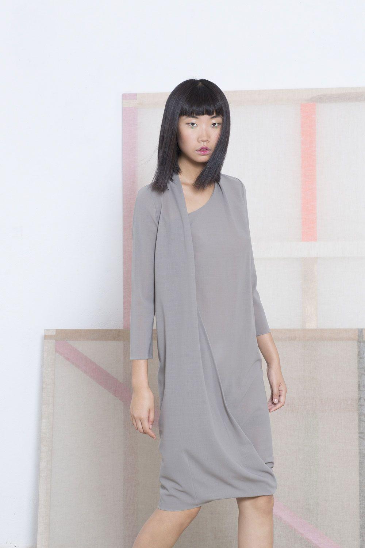 Vestido envolvente con cuello asimétrico drapeado y con manga francesa realizado en voile de lana stretch.