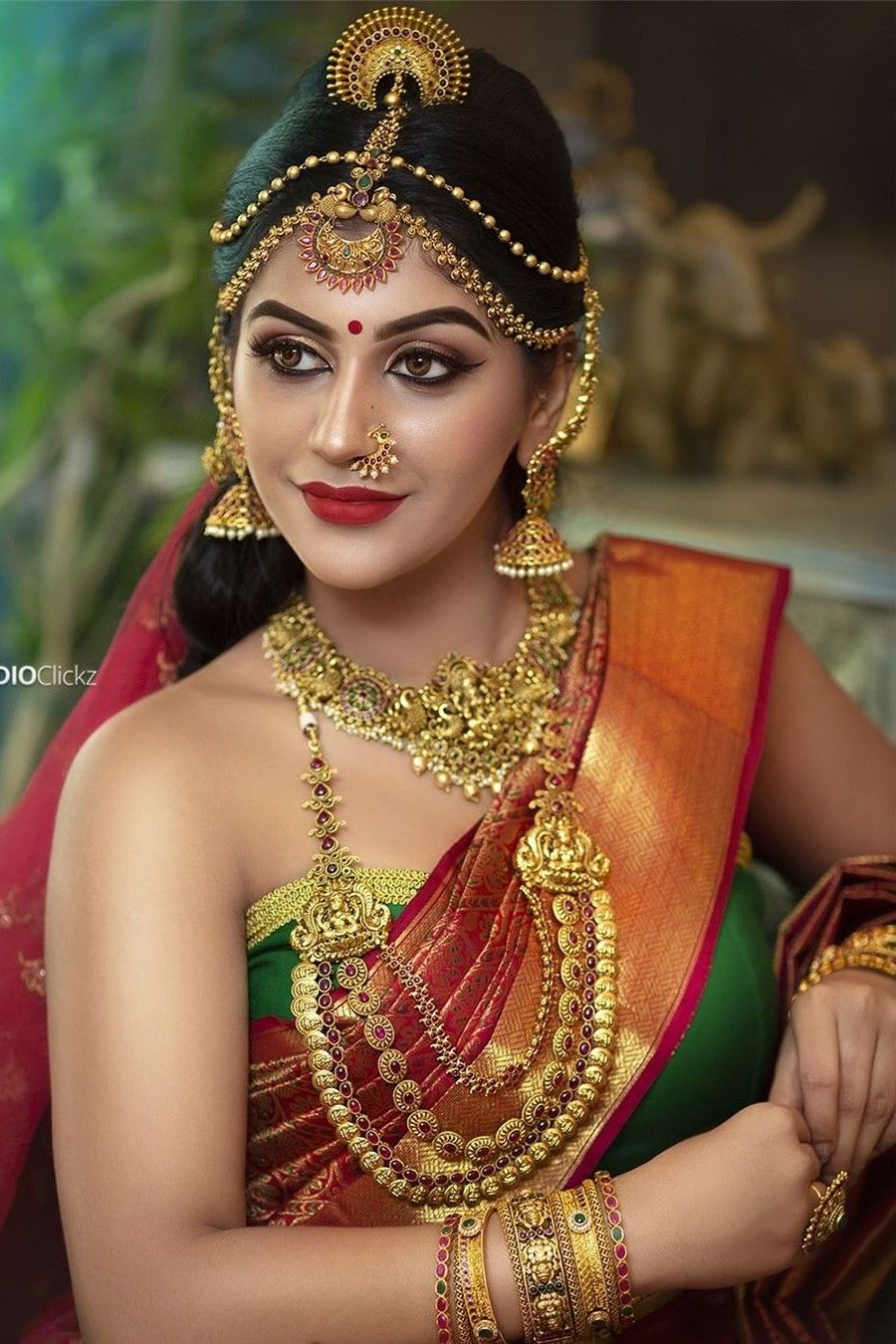Photo of In a bridal look in a red color pattu / kanjeevaram saree, green color elbow len…