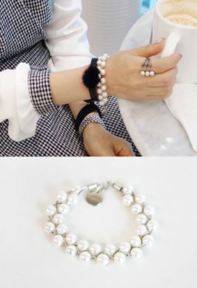 Miamasvin Tiered Pearl BraceletTiered pearl bracelet. Perfect with a houndstooth shift dress with textured black tights and black boots.- Mid-sized pearls Lobster claw closure- Color: Ivory