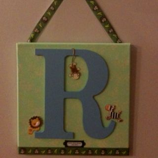 Canvas with wood letter for initial.  Costs about $15.00 to make.  Makes great baby shower, wedding, or housewarming gift.