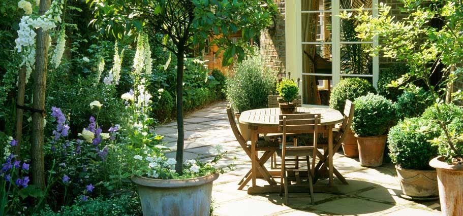 A pretty patio area love how the pots of green bushes softens the stone patio and brick wall - Garden ideas london ...