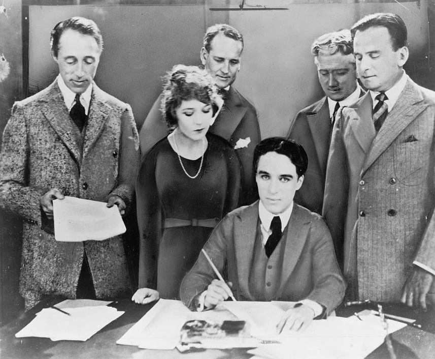 D.W. Griffith, Mary Pickford, Charlie Chaplin (seated) and Douglas Fairbanks at the signing of the contract establishing United Artists motion picture studio in 1919. Lawyers Albert Banzhaf (left) and Dennis F. O'Brien (right) stand in the background.    Source: Library of Congress