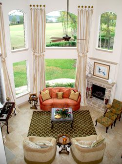 This two story living room uses a neutral color scheme - Living room window treatments for large windows ...