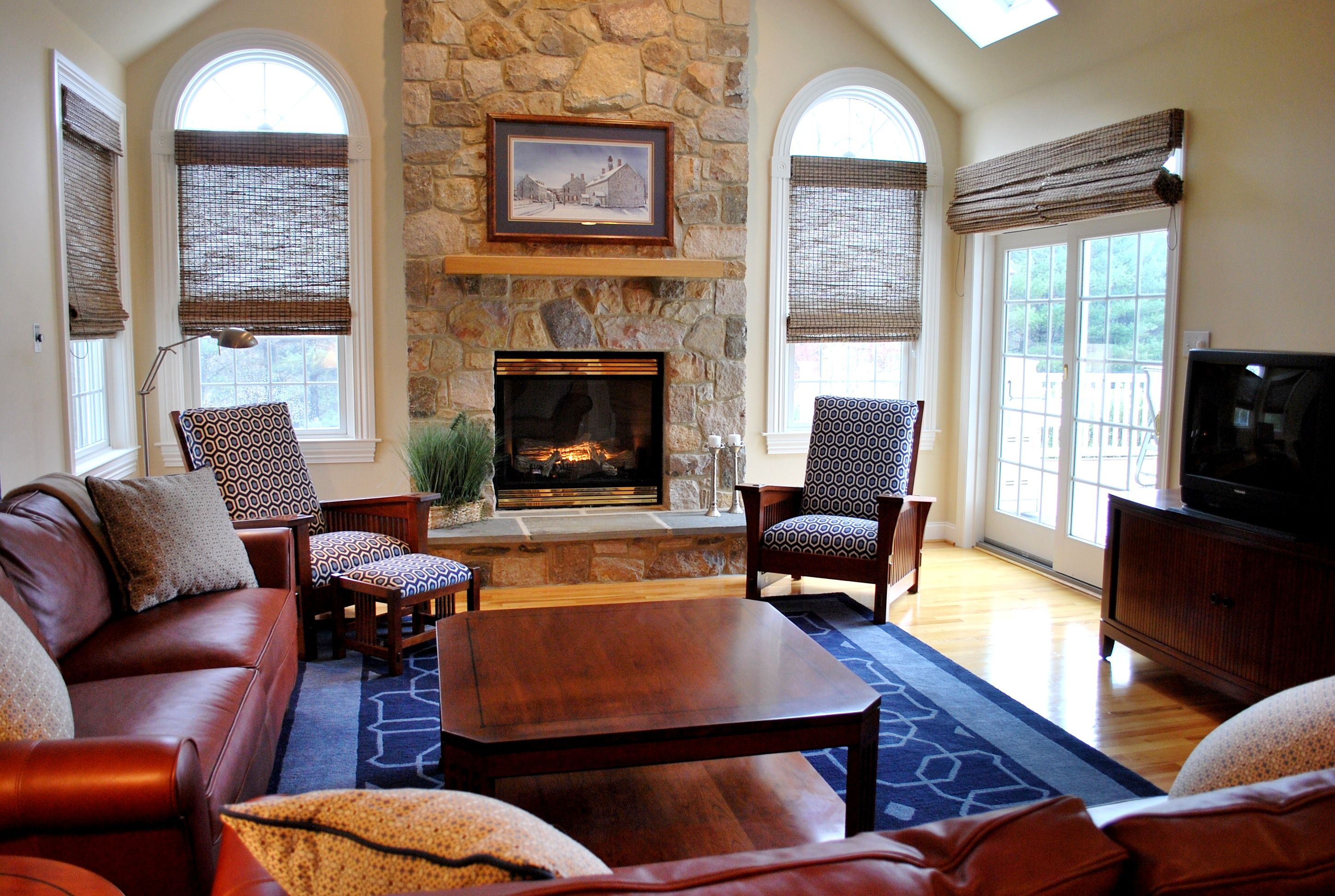 traditional living room with a stone fireplace, vaulted ceiling with