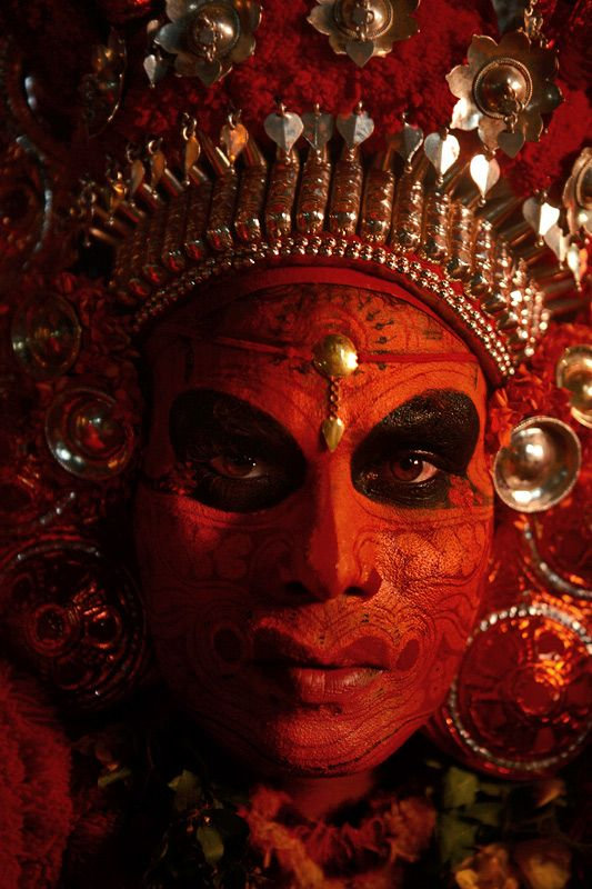 Theyyam performer. The Theyyam can be described as a performance that merges colour, dance, music, poetry and ceremonial rituals. Theyyams take place around the North Kerala district of Kannur. India